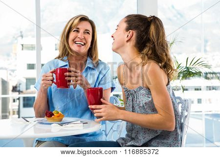 Mother and daughter eat breakfast at home in the kitchen