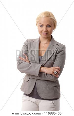 Portrait of attractive young confident businesswoman standing arms crossed.