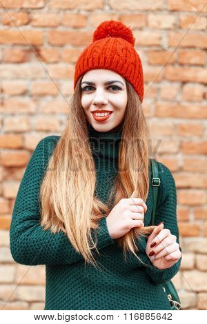 Beautiful Cute Girl In A Red Cap And Green Knitted Jacket Standing Near Red Brick Wall