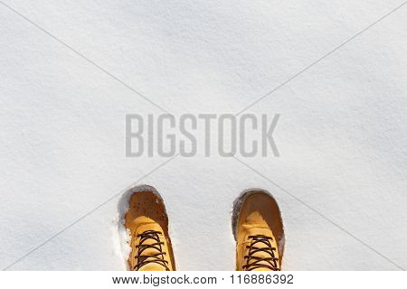Human Legs With Leather Yellow Boots Standing In The Snow. Top View