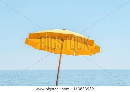 yellow umbrella near sea under blue sky