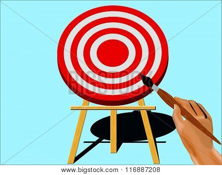 Hand With Paint Brush Getting Ready To Paint on A Target Mounted On An Easel