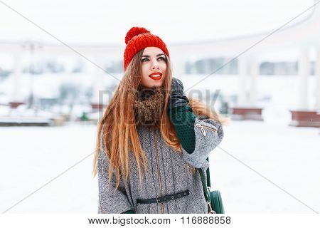 Young Cute Girl With A Beautiful Smile In A Red Knitted Hat And Coat On A Winter Day