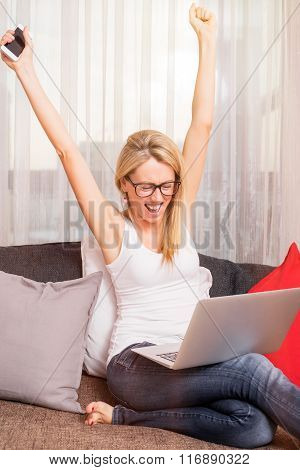 Close-up of woman celebrating her success with computer in her lap and cellphone in her hand