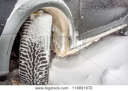 Car Wheel Covered With Snow On A Winter Day