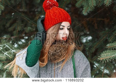 Young Stylish Girl In A Red Cap And Green Sweater Standing On The Background Of Spruce