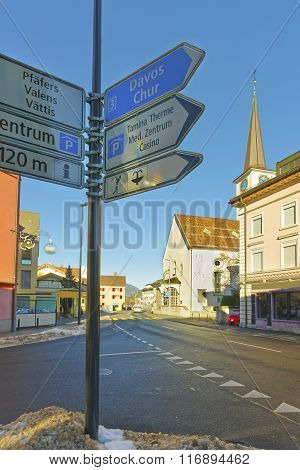 Road sign and Catholic Church in Bad Ragaz. Bad Ragaz is a city in canton St. Gallen in Switzerland. It lies over Graubunden Alps. Spa and recreation village is at end of Tamina valley