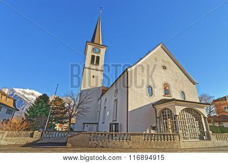 Catholic Church and Mountains in the City of Bad Ragaz. Bad Ragaz is a city in canton St. Gallen in Switzerland. It lies over Graubunden Alps. Spa and recreation village is at end of Tamina valley