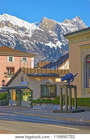 BAD RAGAZ SWITZERLAND - JANUARY 5 2015: Cat statue and Mountains. Bad Ragaz is a city in St. Gallen in Switzerland. It lies over Graubunden Alps. Spa and recreation is at the end of Tamina valley