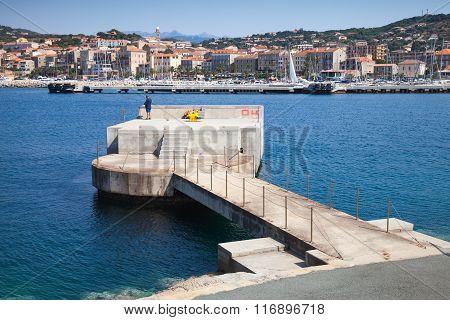 Fisherman On Concrete Pier In Port Of Propriano