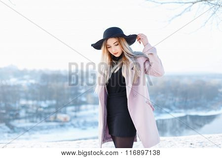 Young Beautiful Girl In Hat And Coat On A Background Of A Winter Landscape