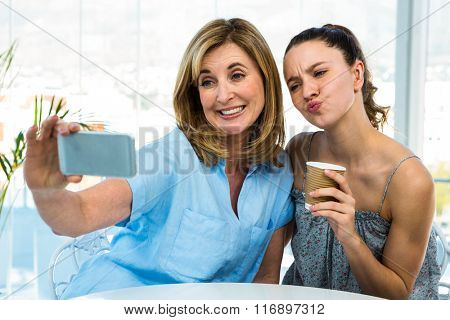mother and daughter take selfie with a phone and grimace