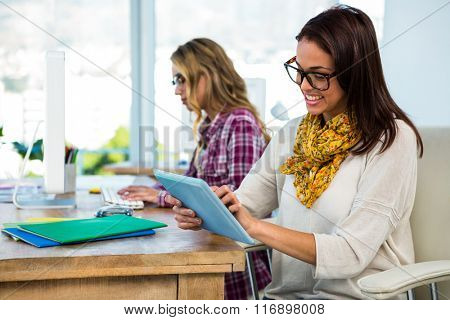 Two girls work at office on computer and tablet