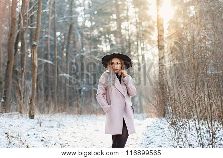 Young Stylish Woman In A Hat And Coat Standing In A Winter Forest At Sunset