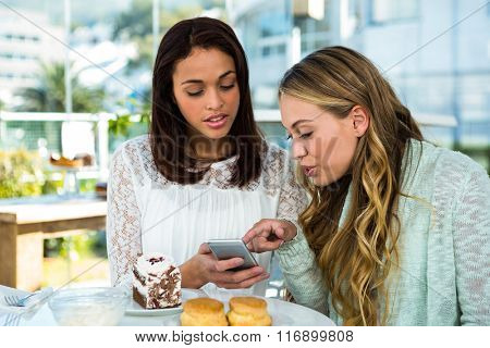 two girls watch a phone while eating
