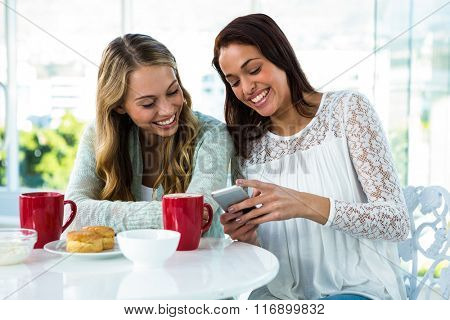 two girls watch a phone while eating and drinking
