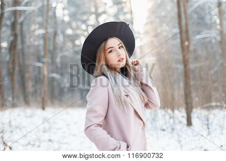 Funny Beautiful Girl In A Hat And Coat On The Background Of A Winter Park On A Sunny Day