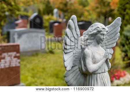 Angel Statue Praying In Front Of Several Tombstones On A Graveyard In Fall