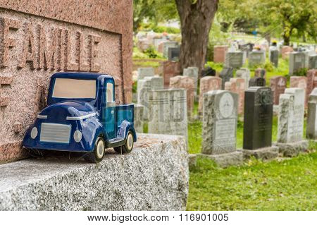 Blue Car Toy On A Tombstone In A Cemetary, Symbolizing The Death Of A Child