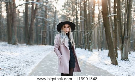 Young Beautiful Woman In Fashionable Stylish Hat And Coat Standing In A Winter Park