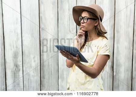 Thoughtful pretty women with glasses holding tablet
