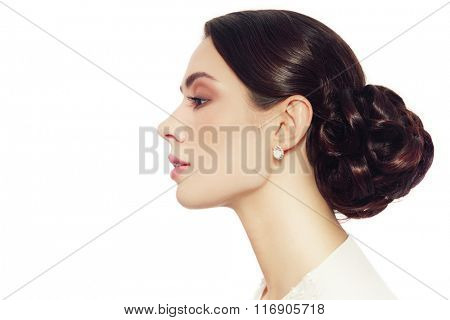 Profile portrait of young beautiful woman with stylish prom hairdo over white background, copy space