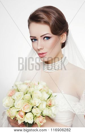 Young beautiful happy bride with stylish make-up, bridal veil and bouquet
