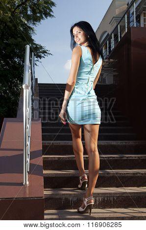 beautiful brunette in blue dress goes on steps