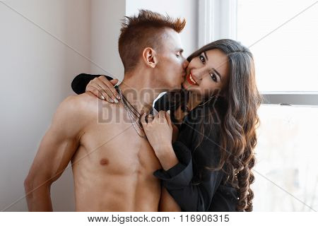 Boy Kisses Girl On The Cheek. Girl Hugging Guy.