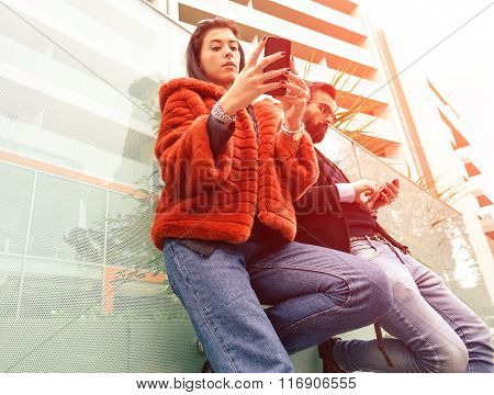 Fashion couple looking their smarphones - Hipster couple in sad moment ignoring each other