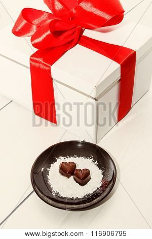 Two Chocolate Heart-shaped Candies On A Brown Plate Next To Gift Box With Red Ribbon