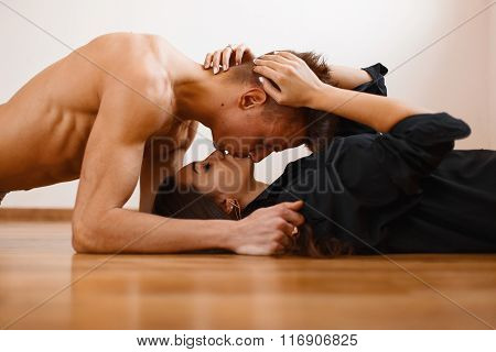 Young Beautiful Couple Kissing On The Wooden Floor. Handsome Man Lying Over The Girl, And Kissing