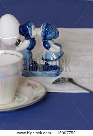 Pretty Porcelain Figurine On A Table Laid For An Early Breakfast