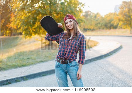 Beautiful Young Hipster Girl In Stylish Clothes Holding A Skateboard And Smiling At Sunset