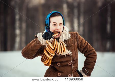 Young  charismatic attractive  woman clothed sheepskin coat and scarf. Girlthe bites off the bagel.