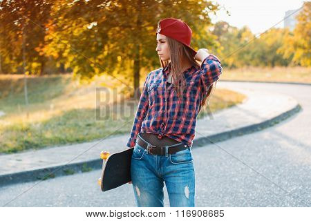 Young Stylish Girl With Skateboard Standing In The Park On A Sunny Day
