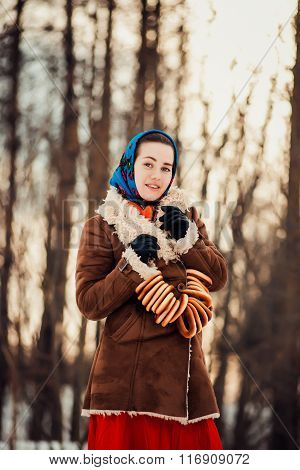 Young  charismatic attractive  woman clothed sheepskin coat and scarf. Girl holding the bagels. Spri