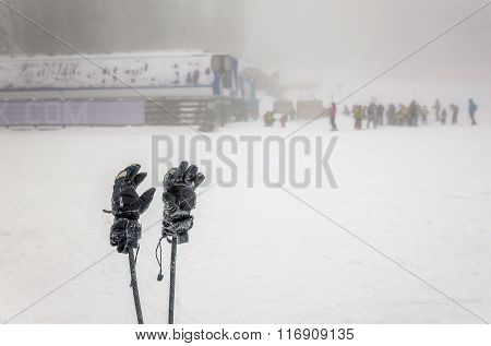 Winter Gloves And Skii Poles With People Skiing On Extreme Weather With Fog In The Background