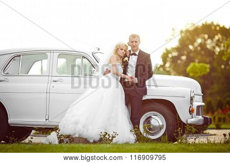 Beautiful Gorgeous Blonde Bride And Stylish Groom On The Background Of Luxury White Car