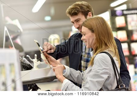 Couple in store choosing digital tablet