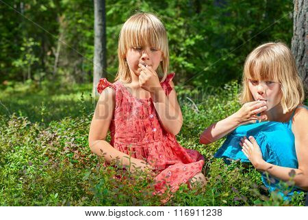 Two little girls wearing blue and red summer dress picking and eating whortleberries in a forest