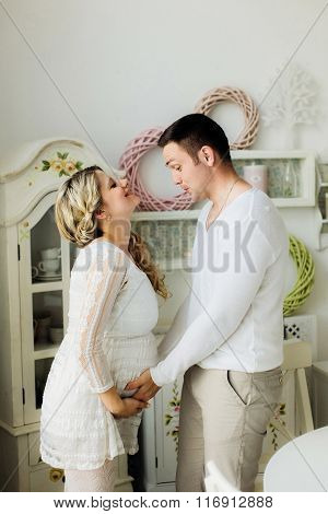 Happy Pregnant Wife With Husband Dressed In White Clothes Lovely Touching Belly At Home.