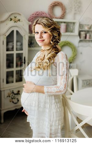 Beautiful Pregnant Woman Caressing Her Belly In White Room.