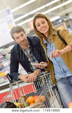Couple in supermarket doing grocery shopping with help of smartphone