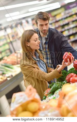 Couple at the grocery store buying fruits and vegetables