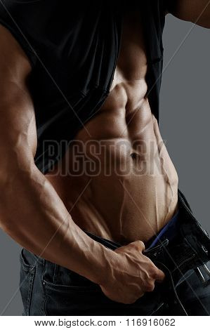 Muscular male torso, shirt and jeans. Silver background.