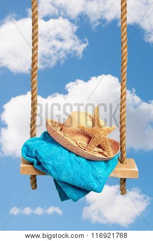 Sunhat with towel on swing in summer sky - idyllic holiday concept