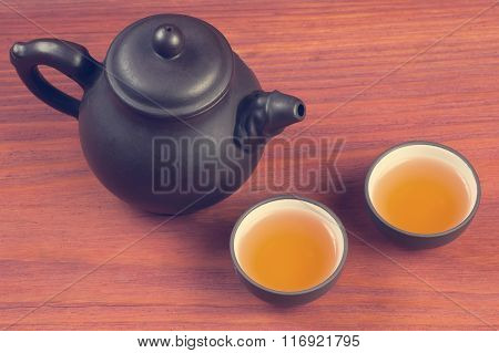 Two clay glazed tea bowls with brewed pu-erh tea and clay teapot on red wooden table vintage filtere