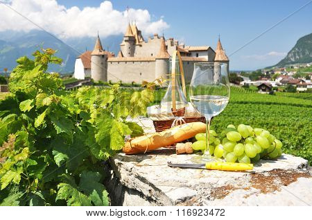 Wine, grapes and bread against old castle. Switzerland