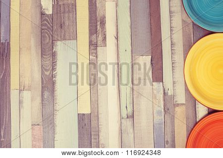 Color Plates On A Wooden Table.